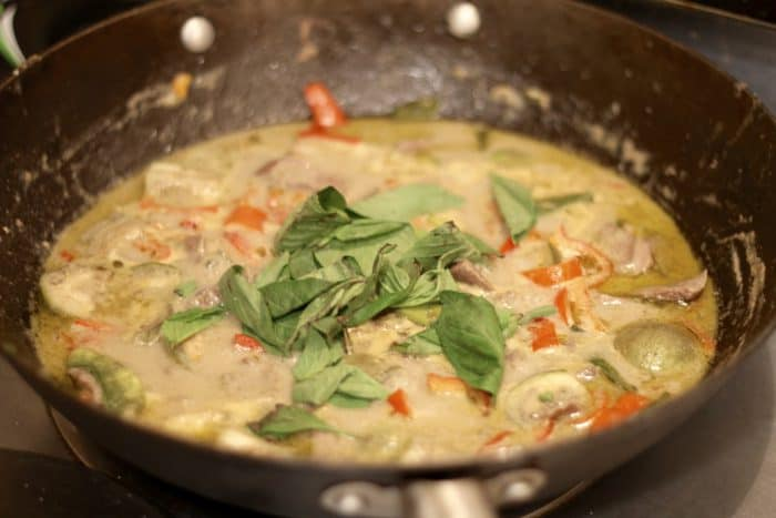 fresh thai basil tossed on the top of cooked green curry in a cast iron pan