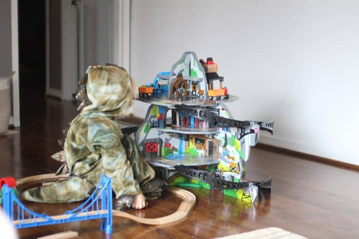 Little toddler in a dinosaur costume playing with this railway mine set from Hape Toys