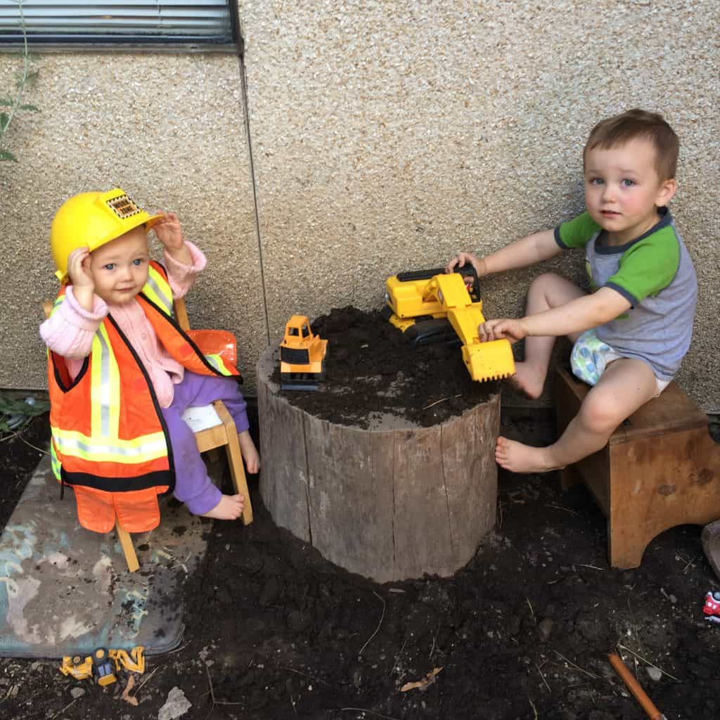 Bob the builder costume on toddlers as they play in the dirt