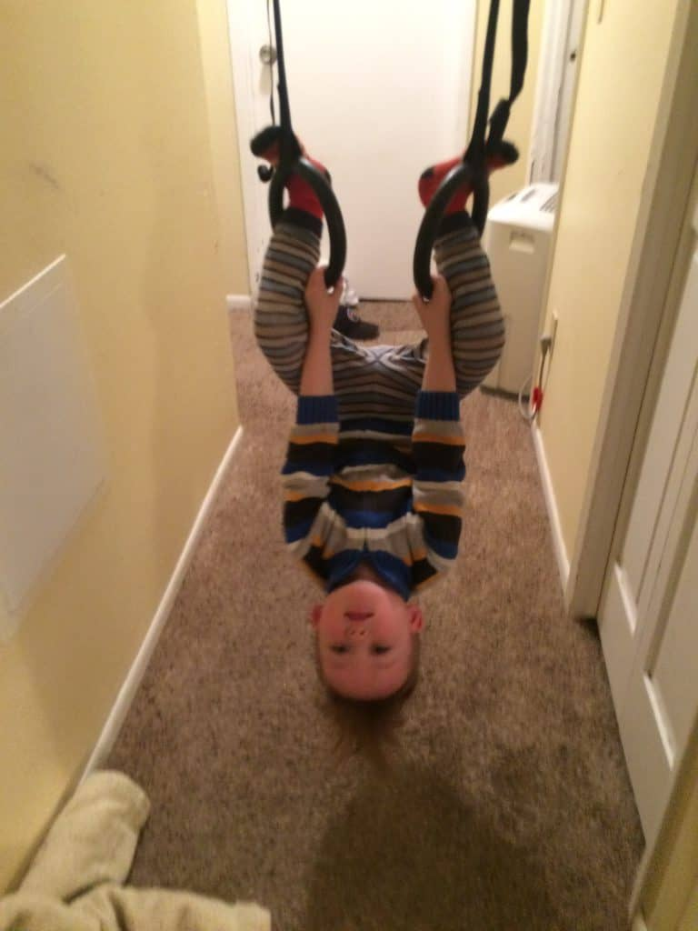 toddler boy swinging in a hallway upside down on gymnastics rings; indoor activities for toddlers