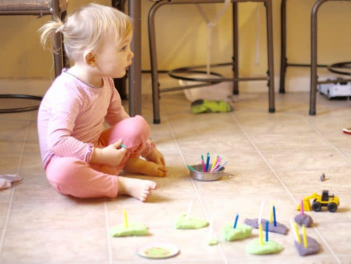 Toddler girl playing Play Doh on the floor with birthday candles, a perfect indoor activity for toddlers