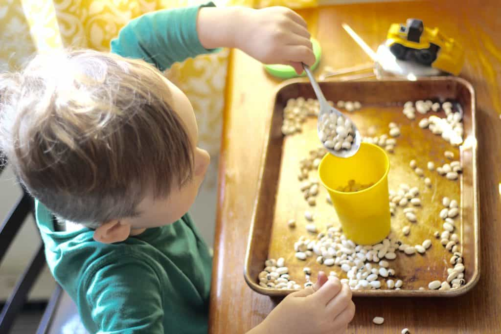 Scooping beans toddler activity