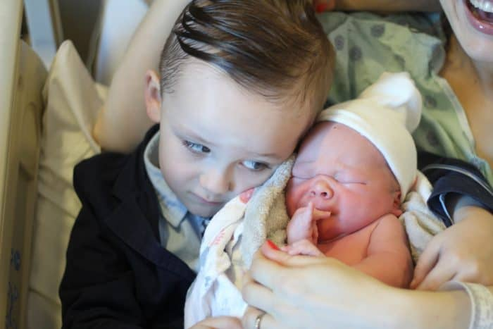 Older brother meeting the third baby and hugging him next to mom in the hospital