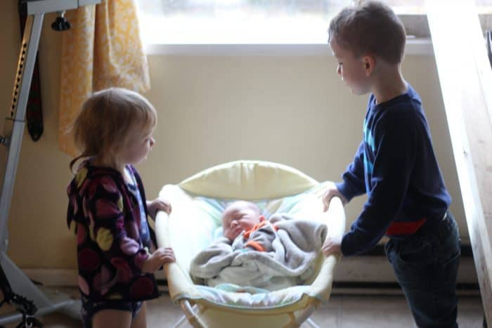 Two siblings meeting their baby brother sleeping in a Rock n Play, the third baby