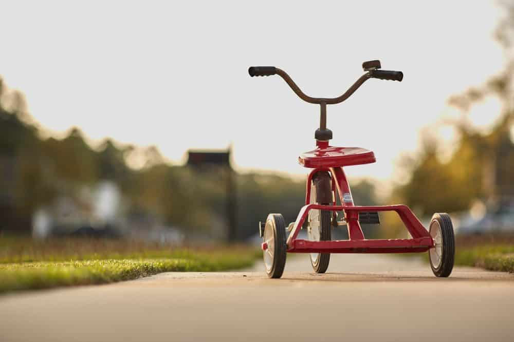 photo of a red tricycle used as cover photo for how to homeschool preschool post