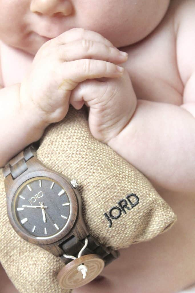 A brown JORD men's wooden watch held by a small baby