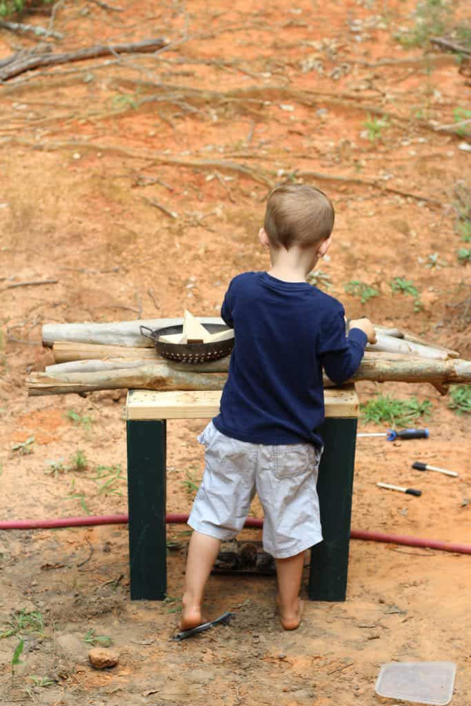 a little boy cooking in an outdoor play kitchen made of small wooden logs.