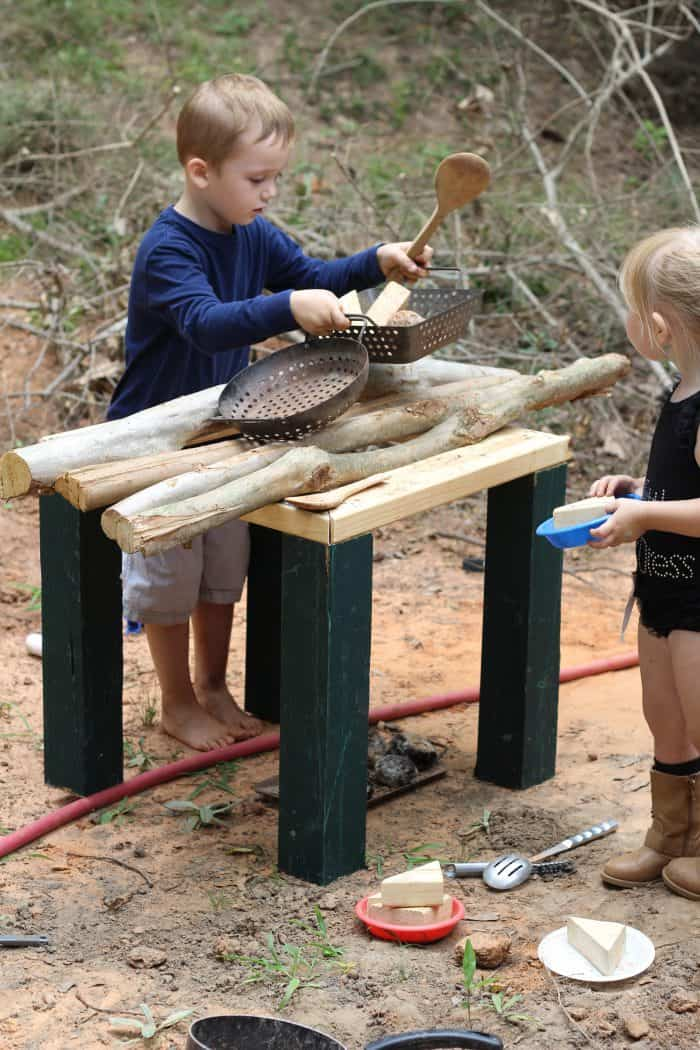 two kids playing outside making pretend food on a wooden diy outdoor play kitchen