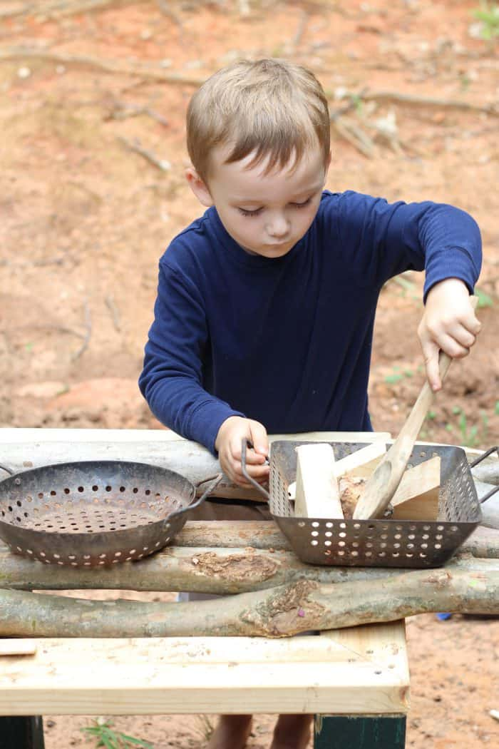 a boy stirring wooden blocks in a diy outdoor play kitchen