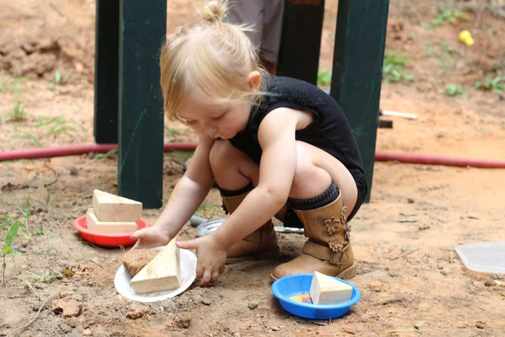 A toddler girl stacking wooden triangles on plastic plates in the dirt.