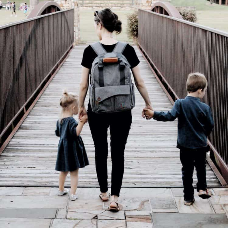 how to be less busy as a mom: a mom walking over a bridge with her daughter and son holding hands