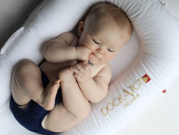 5 month old baby resting in a white DockaTot deluxe sucking on his hands and toes