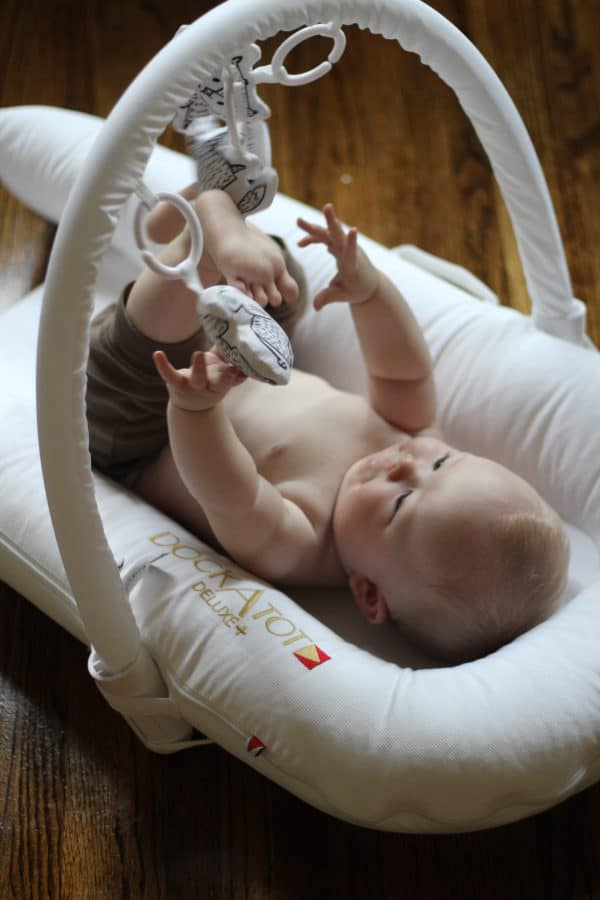baby on his back playing with the toy arch above his white DockaTot