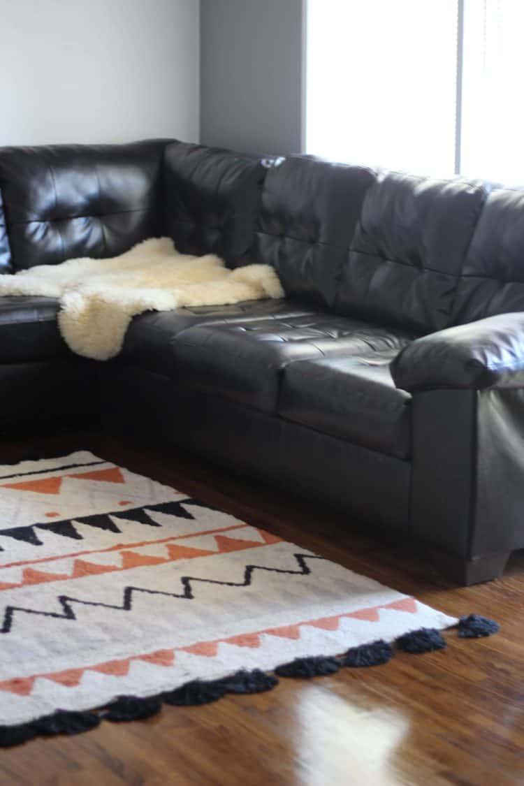 a brown leather couch with a soft lorena canals washable rug