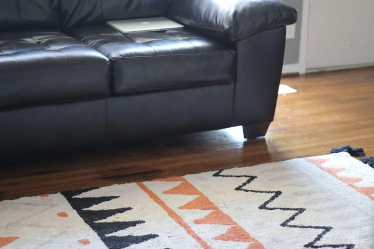 lorena canals rug in black and orange terracota next to a brown leather couch