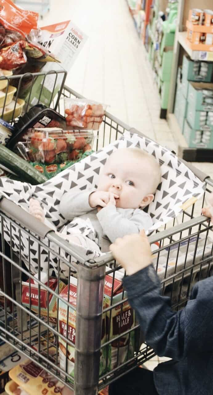 Shopping  cart full of groceries with the baby in a Binxy Baby Hammock
