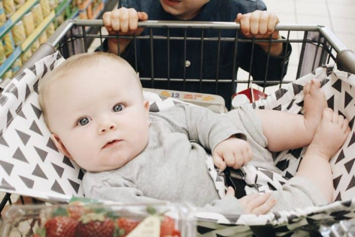 baby boy riding in a Binxy Baby shopping cart hammock in tribal print