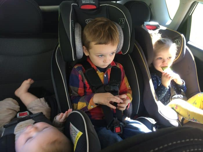 Kids sitting in three narrow car seats to fit 3 across