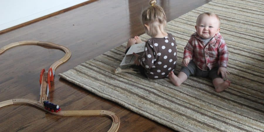 a baby and toddler sitting on a golden rug with green stripes from rug shop and more