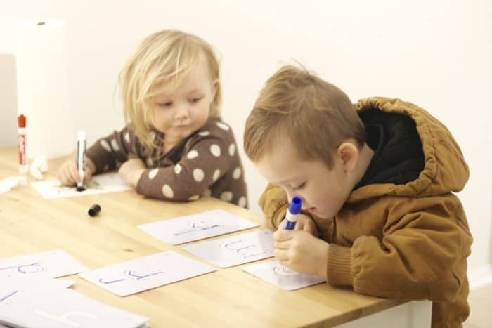 Preschoolers learning to write on wipeable Kumon letter flashcards, using an erasable marker