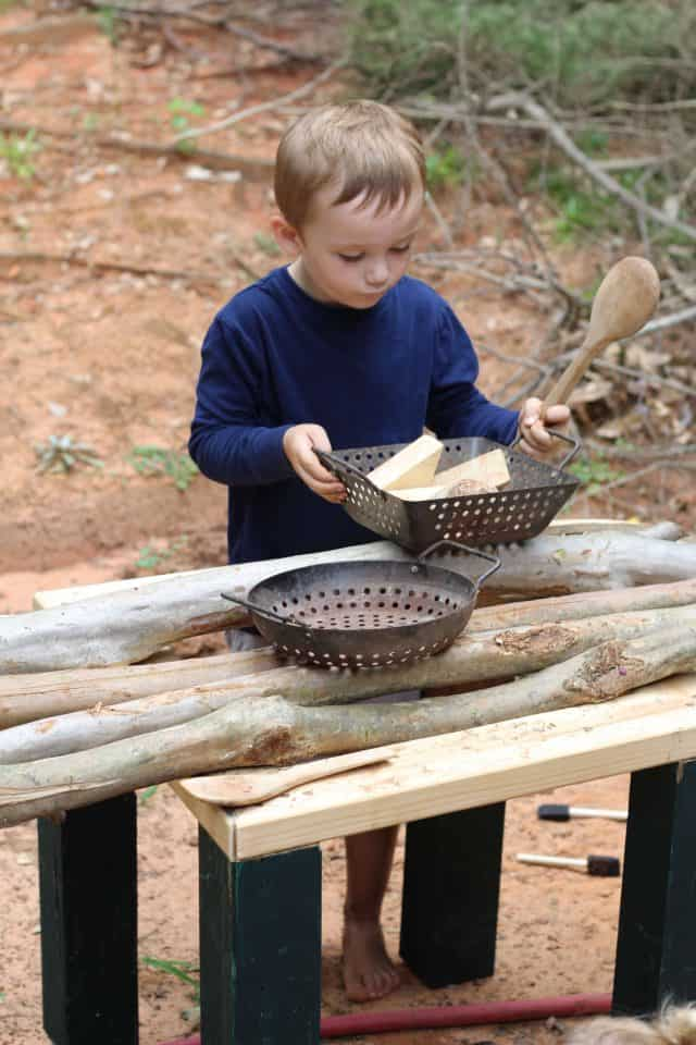 preschool boy playing outside in an outdoor play kitchen, part of a homeschool preschool
