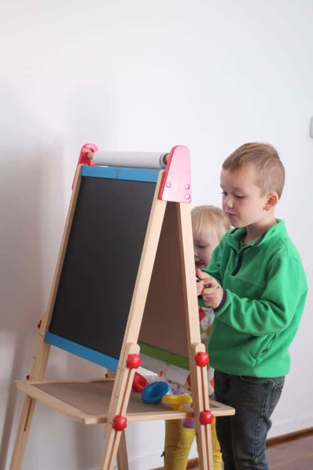 Hape chalk board, white board, and paper art easel being used for homeschool preschool