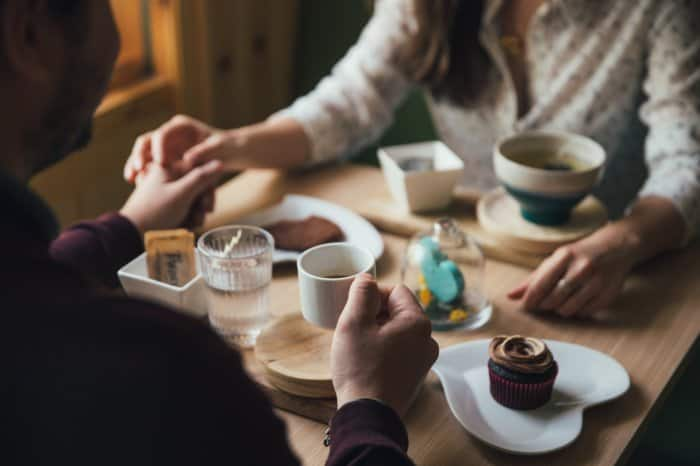a couple holding hands as they hold coffee mugs at a restaurant