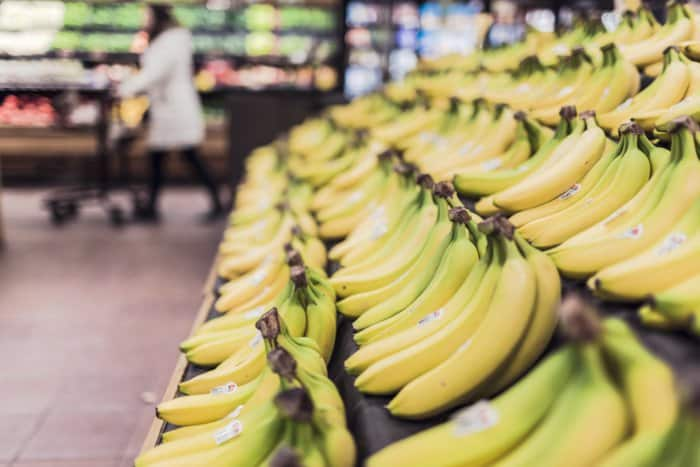 a close up of the banana isle at the store full of yellow bananas