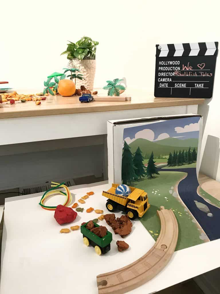 all the materials needed to make a stop-motion video with Goldfish crackers including a backdrop and set made of dirt, train, tracks, and dump truck.