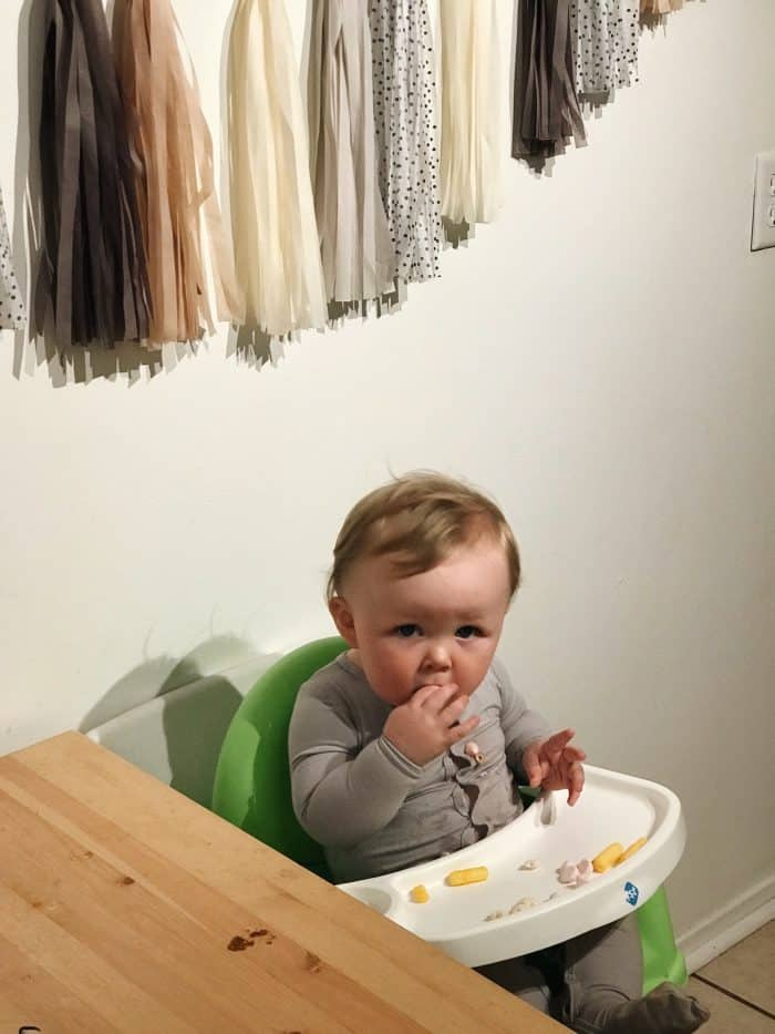 a baby picking up baby led weaning foods from his highchair and bringing them to his mouth