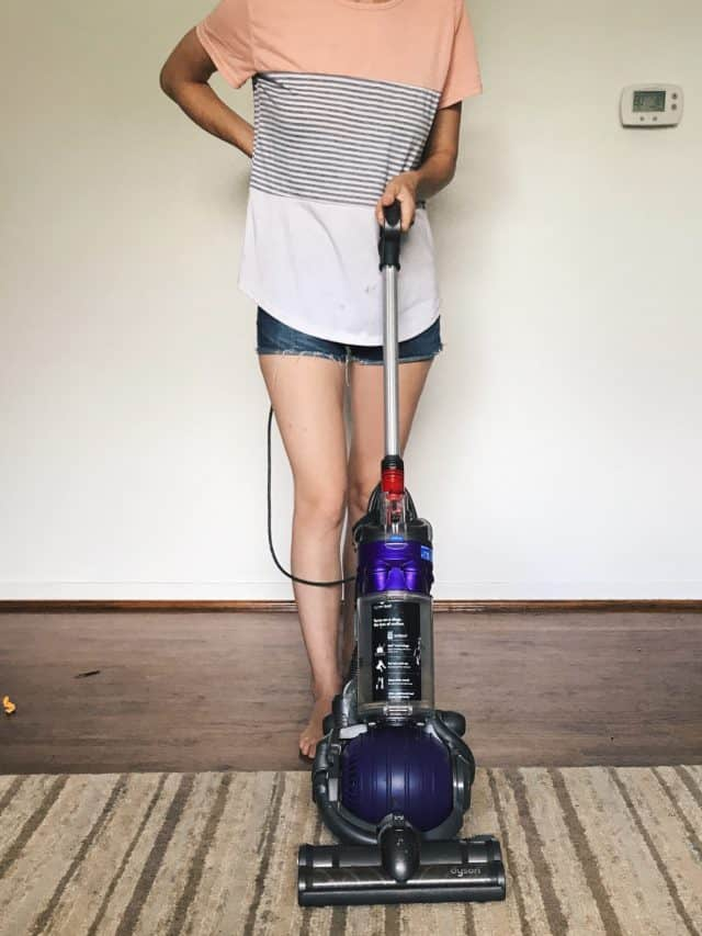 A woman vacuuming with a Dyson vacuum doing daily house cleaning