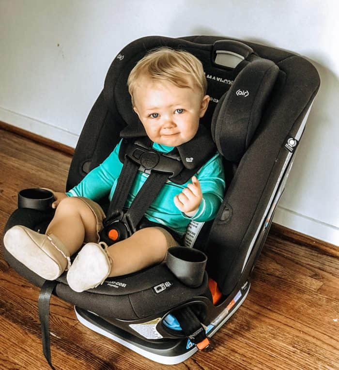 baby boy sitting in a new Black Maxi-Cosi Car Seat wearing a teal shirt