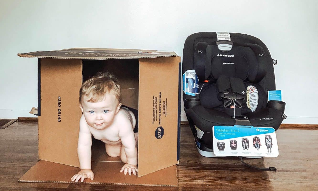 Baby peeking out of a box after unboxing a Maxi-Cosi Magellan Convertible Car Seat