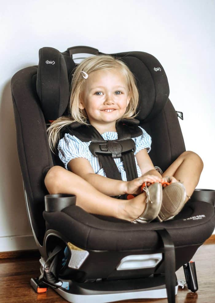 A 3 year old girl stares at the camera while being fit for her new Maxi-Cosi Magellan 5-in-1 convertible Car Seat in Black