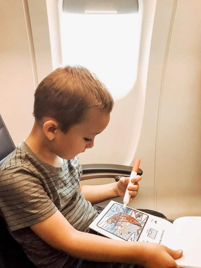 5 year old boy coloring a Melissa and Doug color blast while flying on an airplane