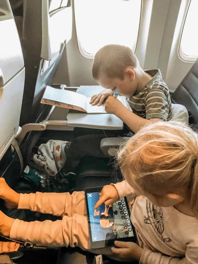 two preschoolers coloring and playing Ipad games during a long flight