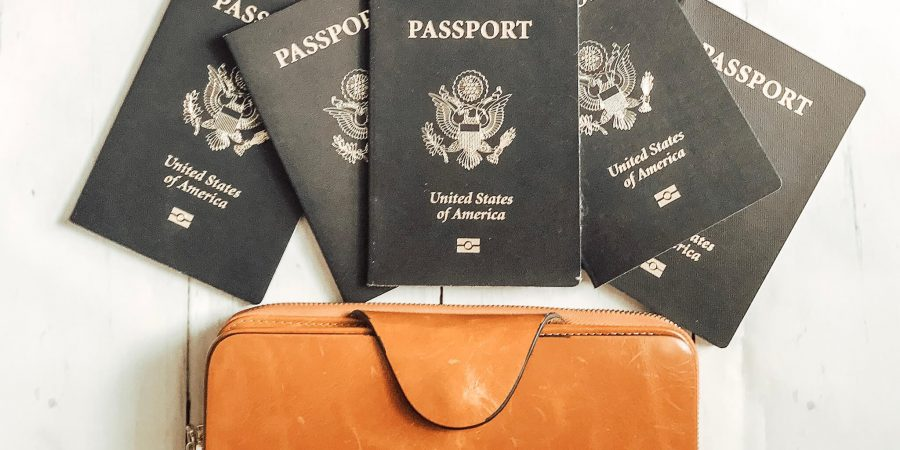 leather wallet and 5 passports laid out on a white wood table