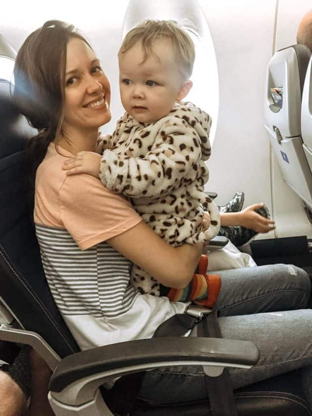 mom holding her toddler on her lap on an airplane