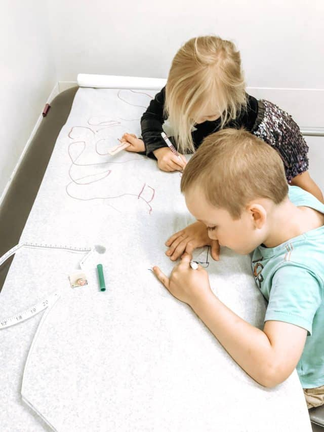 a 3 and 5 year old coloring with markers on the doctor's table waiting for the nurse to arrive.
