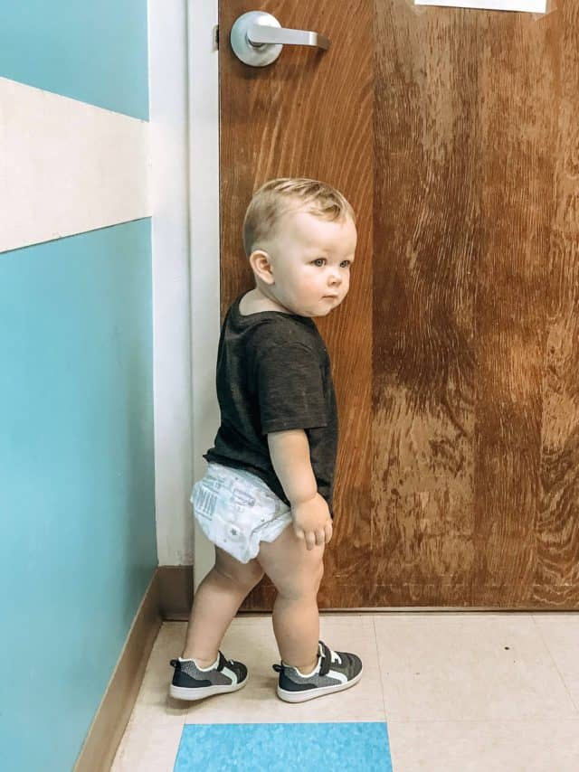 a toddler exploring the waiting room with blue walls before the doctor arrives.