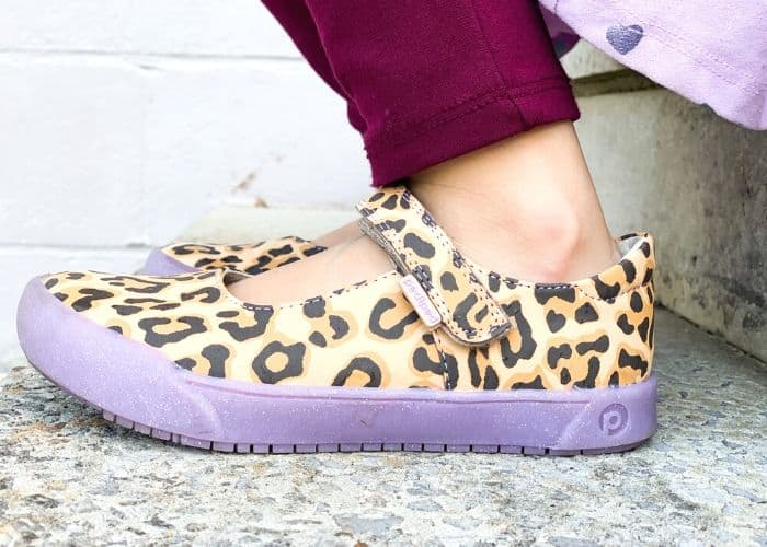 a cheetah print mary jane style shoe with purple sole on a little girl