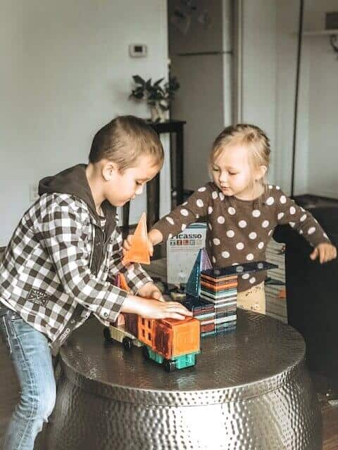 Picasso tiles 180 piece magnetic tile set being played with by two kids on a shiny metal table.