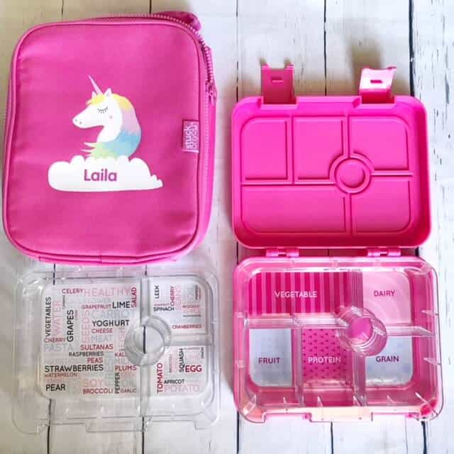 hot pink bento box with clear plastic tray, and a matching hot pink cooler with unicorn on the front.