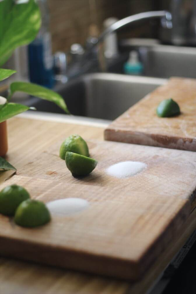 Salt and lime juice on a wooden cutting board used to remove garlic and onion smell