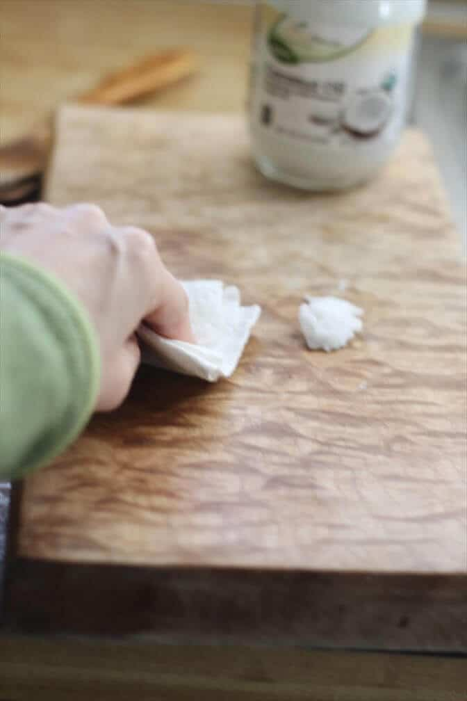 Rubbing coconut oil into a wooden cutting board to season.