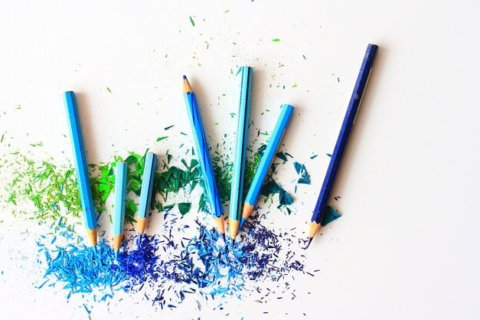 blue and green colored pencil shavings on a white table