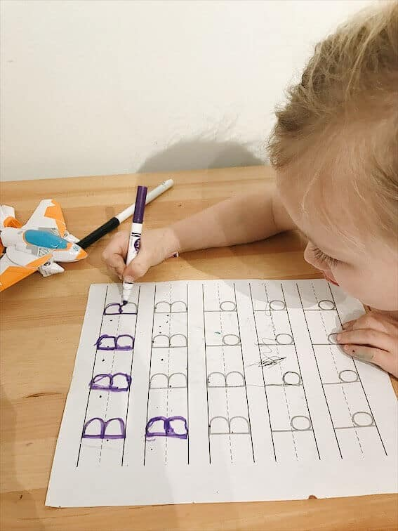 preschooler tracing the letter B uppercase and lowercase while learning to write