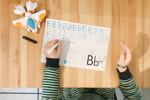 a preschooler learning to write the letter b