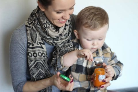 a mom feeding her toddler baby food from a jar, one way for busy moms to save time on the go.