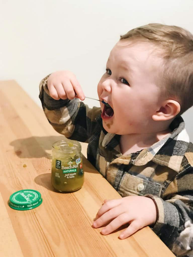 toddler feeding himself beech-nut naturals apple and kale baby food
